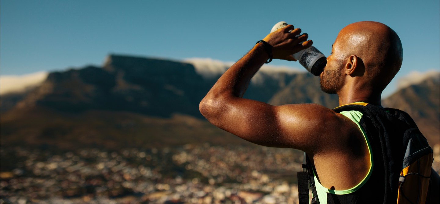 Male athlete drinking water while training outside wearing a Libre Sense Glucose Sport Biosensor