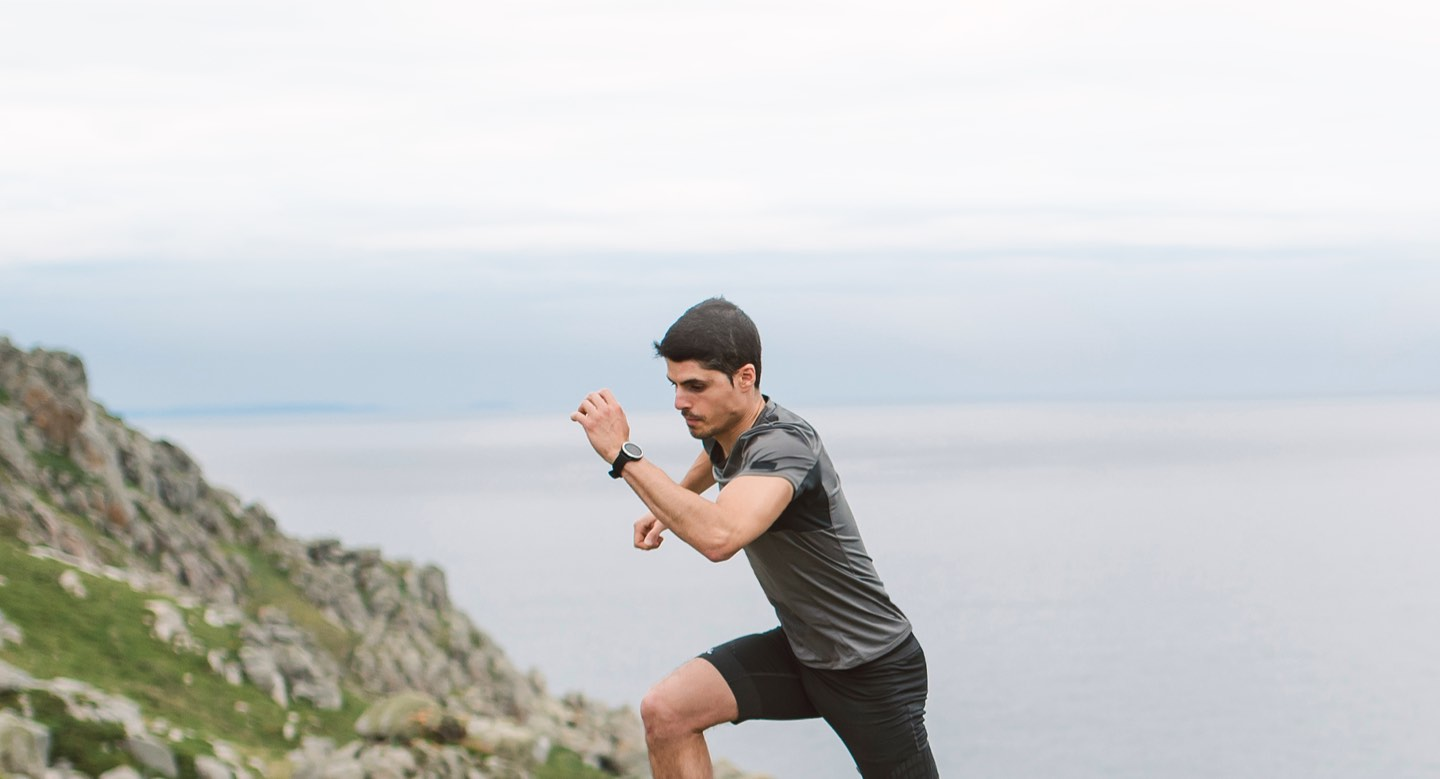 Man wearing Libre Sense Glucose Sport Biosensor while running up rocky coastal hill